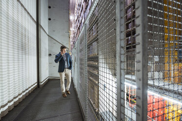 Man in automatized high rack warehouse talking on cell phone - DIGF01784