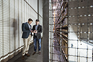 Two men in automatized high rack warehouse looking at tablet - DIGF01787
