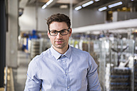 Portrait of confident businessman in factory shop floor - DIGF01835