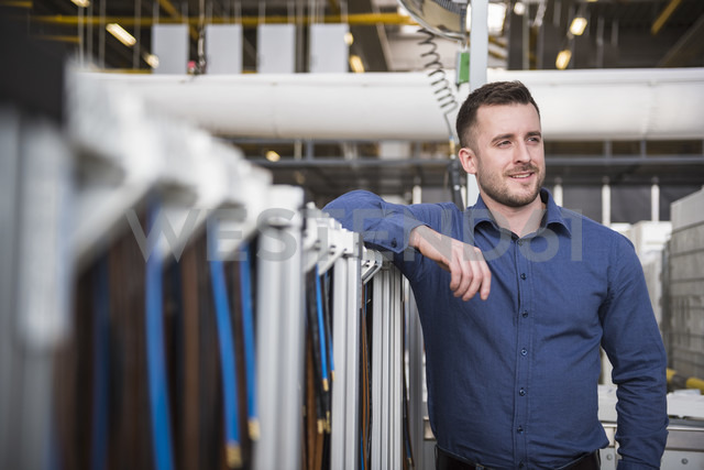 Portrait of confident businessman in factory shop floor - DIGF01841