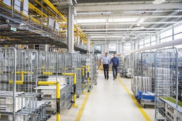 Two men walking in factory shop floor - DIGF01847