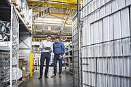 Two men with tablet talking in factory shop floor - DIGF01853