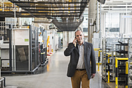 Businessman in factory shop floor talking on the phone - DIGF01856