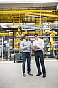 Two men with tablet talking in factory shop floor - DIGF01859
