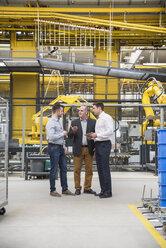 Three men with tablet talking in factory shop floor - DIGF01862
