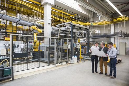 Three men with blueprint talking in factory shop floor - DIGF01868