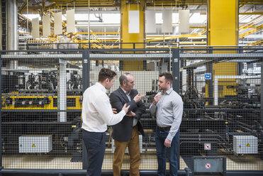 Three men talking in factory shop floor - DIGF01871