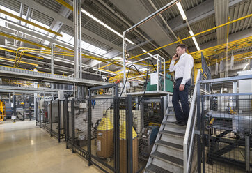 Businessman in factory shop floor talking on the phone - DIGF01874