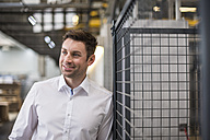 Portrait of confident businessman in factory shop floor - DIGF01877