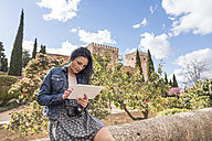 Spain, Granada, young woman using tablet at the Alhambra - JASF01729