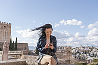 Spain, Granada, smiling young woman using cell phone at the Alhambra - JASF01732