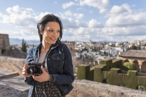 Spain, Granada, smiling young woman with camera at the Alhambra - JASF01735
