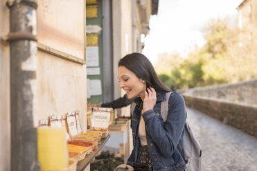 Spain, Granada, happy young woman at Albayzin district shopping for spices - JASF01747
