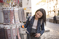 Spain, Granada, smiling young woman at Albayzin district at a souvenir stall - JASF01750