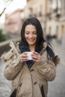 Spain, Granada, smiling young woman holding cup at Albayzin district - JASF01756