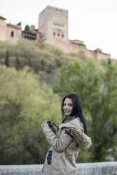 Spain, Granada, smiling young woman taking pictures at the Alhambra - JASF01759