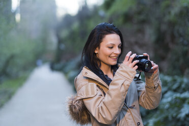 Smiling young woman holding camera outdoors - JASF01762