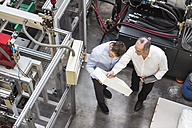 Top view of two men in factory shop floor talking about product - DIGF01894