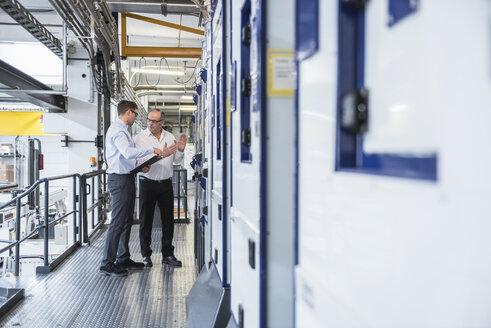 Two men talking in factory shop floor - DIGF01909