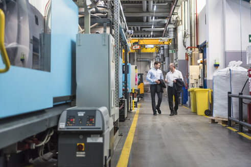 Two men walking and talking in factory shop floor - DIGF01924