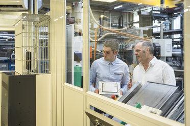 Two men talking in factory shop floor - DIGF01942