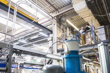 Two men talking in factory shop floor - DIGF01951