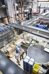 Top view of two men talking in factory shop floor - DIGF01960