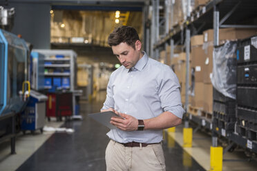 Man using tablet in factory warehouse - DIGF01969