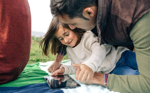 Happy girl and her father using tablet lying on blanket outdoors - DAPF00704