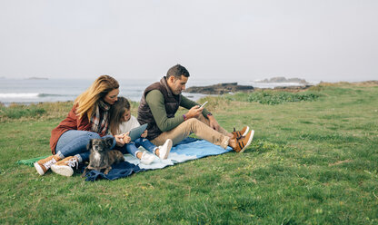 Family with dog sitting on blanket at the coast using wireless devices - DAPF00707