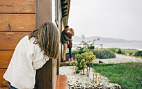 Back view of little girl spying couple in love kissing next to wooden house - DAPF00710