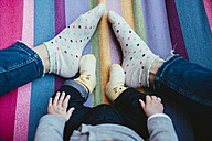 Feet of mother and baby girl on a hammock - GEMF01594