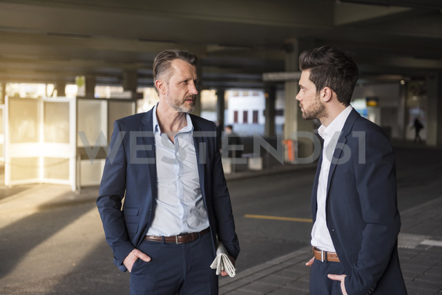 Two businessmen talking at bus terminal - DIGF01981 - Daniel Ingold/Westend61