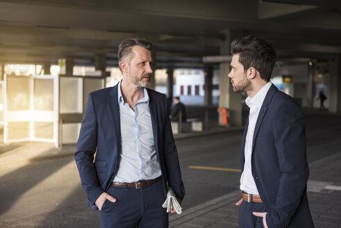 Two businessmen talking at bus terminal - DIGF01981