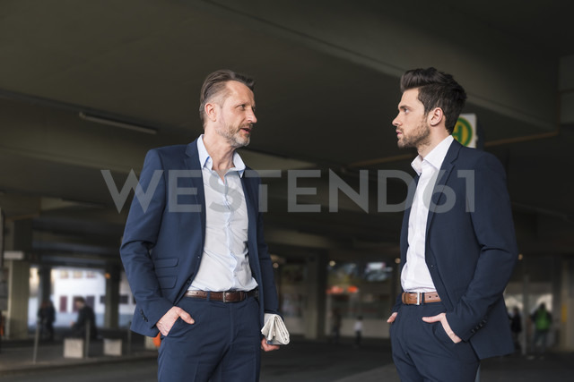 Two businessmen waiting at bus terminal - DIGF01996 - Daniel Ingold/Westend61