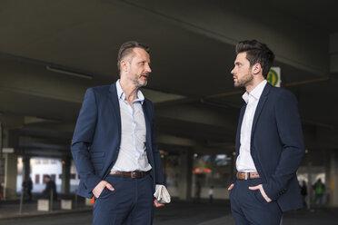 Two businessmen waiting at bus terminal - DIGF01996