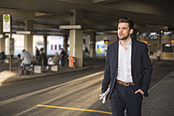 Portrait of young businessman waiting at bus terminal - DIGF02002