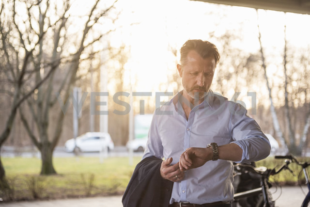 Portrait of mature man checking the time - DIGF02005 - Daniel Ingold/Westend61
