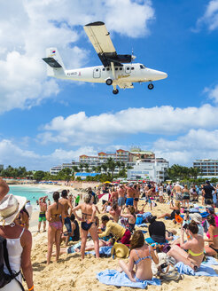 Caribbean, Sint Maarten, Philippsburg, Simson Bay Village, tourists on beach watching plane approaching airport - AM05379