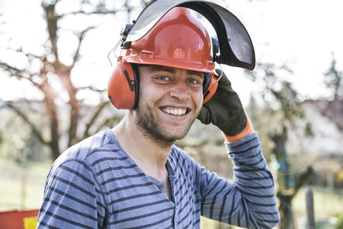 Young man wearing working helmet and ear defenders, portrait - MAEF12193