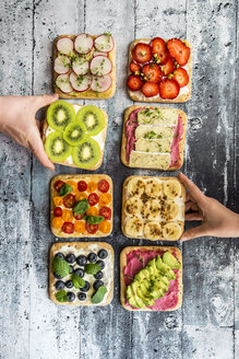 Children's hands taking garnished sandwiches - SARF03304