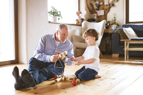 Grandfather and grandson playing music at home - HAPF01506