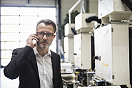 Businessman in factory shop floor on the phone - DIGF02019