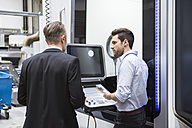 Two men talking at control in modern factory - DIGF02028