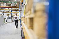 Man walking in storehouse taking notes - DIGF02040