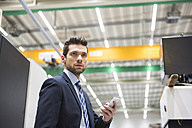 Businessman in factory shop floor holding cell phone - DIGF02043