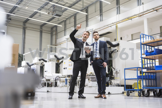 Two businessmen with tablet talking in factory shop floor - DIGF02046 - Daniel Ingold/Westend61