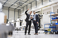 Two businessmen with tablet talking in factory shop floor - DIGF02046