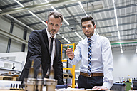 Two businessmen at table in factory shop floor examining product - DIGF02052