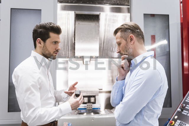 Two men in factory discussing product - DIGF02073